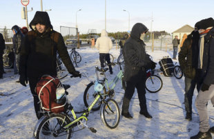 Refugees and migrants gather near a check point on the Russian-Norwegian border outside Nickel (Nikel) settlement in Murmansk region, Russia, October 30, 2015. The flow of Middle Eastern migrants trying to reach Europe via the Russian Arctic slowed dramatically on October 29, partly due to a shortage of bicycles to cross the border, a source who deals with them told Reuters. According to officials, many Syrians obtain business or study visas to enter Russia and then travel through Moscow and Murmansk to Nickel, a town of some 12,000 population named after the metal mined there. REUTERS/Fyodor Porokhin - RTX1TYD7